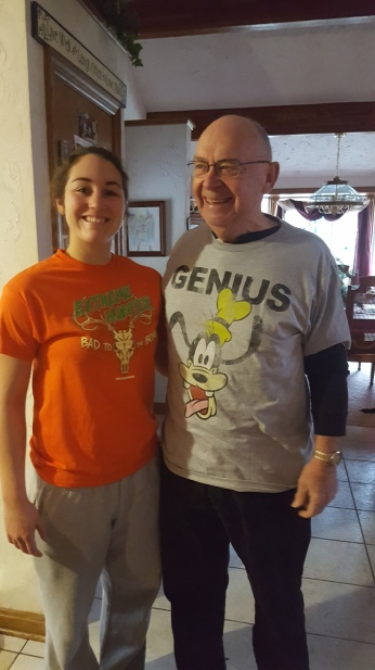 ALYSSA WITH HER GRANDFATHER IN THEIR SHIRTS THEY GOT EACH OTHER SINCE THEY COULDN'T WAIT UNTIL CHRISTMAS. ALYSSA WAS BORN ON HER GRANDFATHER'S BIRTHDAY.