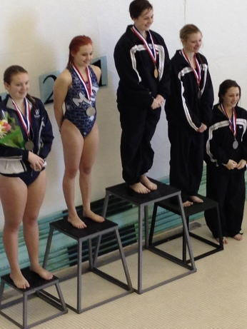 ALLISON WINNING HER MEDAL ON SENIOR NIGHT. ALLISON IS THE SWIMMER ON THE LEFT WITH A BOUQUET OF FLOWERS.