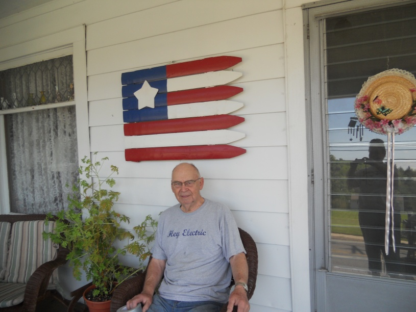 DAD SITTING BESIDE THE CITRONELLA PLANT WITH THE AMERICAN FLAG DECORATION HANGING OVERHEAD.