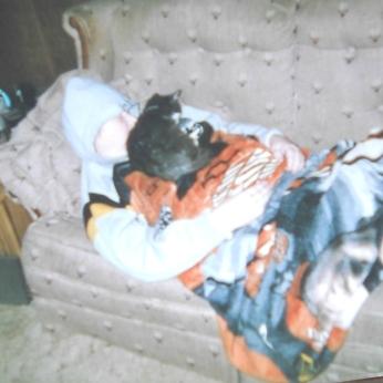 DAISY MAE AS A KITTEN LAYING ON MY TONY STEWART FLEECE BLANKET ON ME.